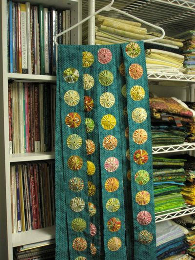 Yo-yo quilt. First the yo-yos are sewn to strips of fabric,